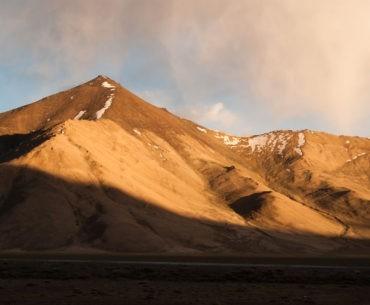 Zachód słońca na Pamir Highway. Promienie schodzą po górze obok naszego obozu.