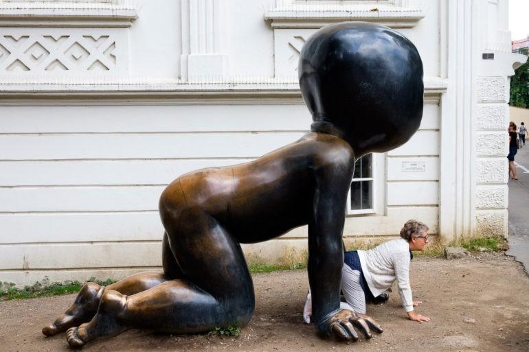 Ludzie w każdym wieku ulegają dzieciom. Rzeźba Davida Černýego na Kampie, okolice Muzeum Sztuki Współczesnej
