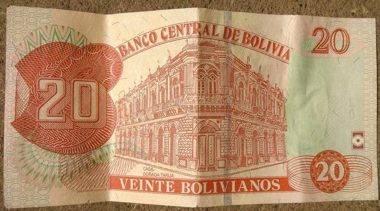 Dwadzieścia boliwijskich pieniążków z budynkiem powyżej