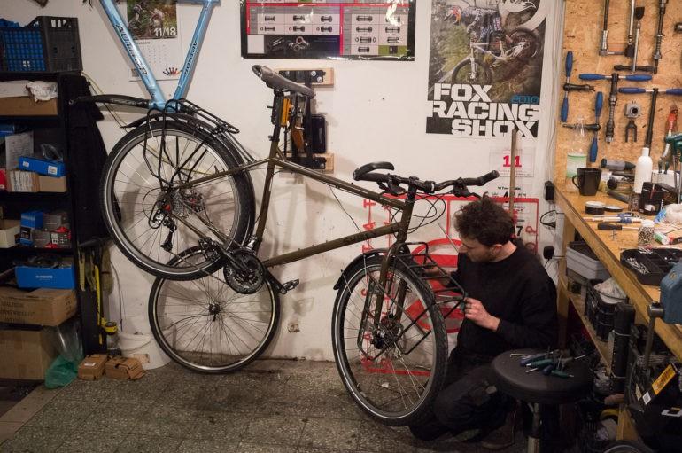Michał wykonuje regulacje przy rowerze