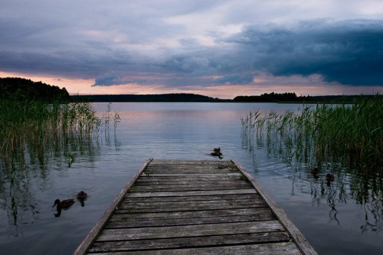 Zachód słońca w Wigierskim Parku Narodowym. Kaczki opływają leciwy drewniany pomost
