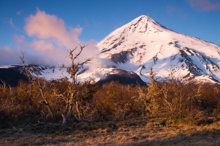 Promienie wschodzącego słońca opierają się o wulkan Lanin