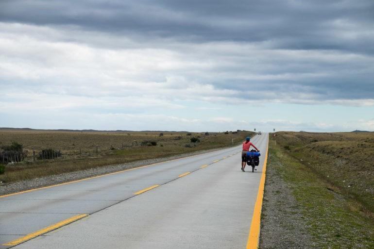 Gosia idzie z rowerem zaciskając zęby na wiatr